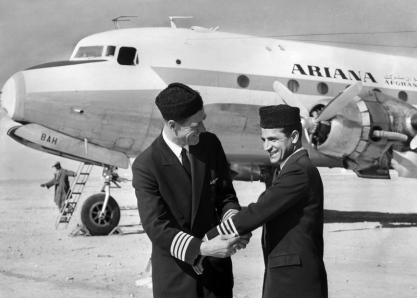 Captain Everett W. Wood, Ariana Chief Pilot and Pan Am instructor, presents pilot stripes to Enaam-ul-Haq Gran. Captain Gran was the first Afghan pilot of Ariana Airlines to receive command status for a four-engine aircraft.